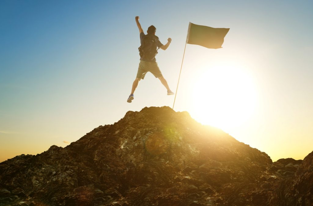 success, leadership, achievement and people concept - silhouette of young guy with flag on mountain top over sky and sun light background